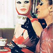 Vintage latex-wearing doxy kisses a chic upper-class lady.