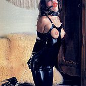 Fine looking vintage lady gagged in dark latex outfit.